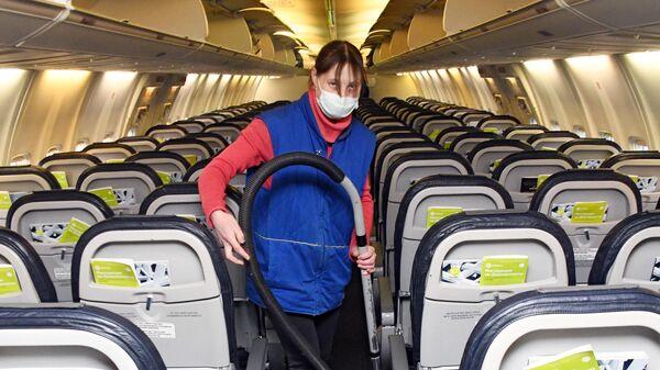 Сотрудница клининговой компании проводит уборку салона самолета в аэропорту Читы
