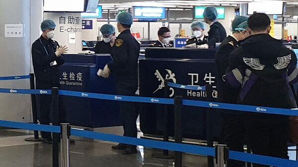 Проверка температуры у туристов в аэропорту Шоуду в Пекине