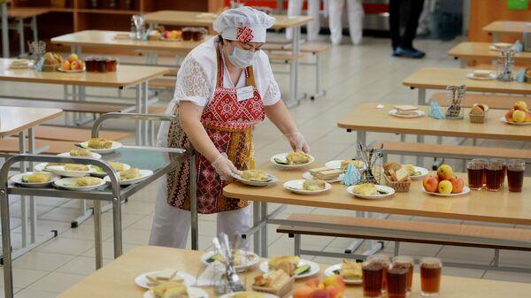 Работница школьной столовой разносит тарелки с едой к обеду учеников