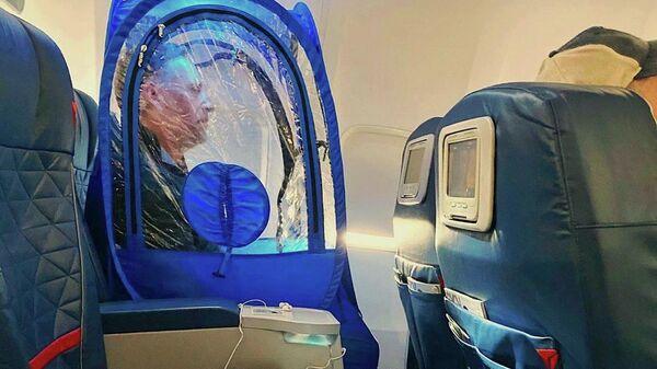 Мужчина в защитном чехле WeatherPod в салоне самолета