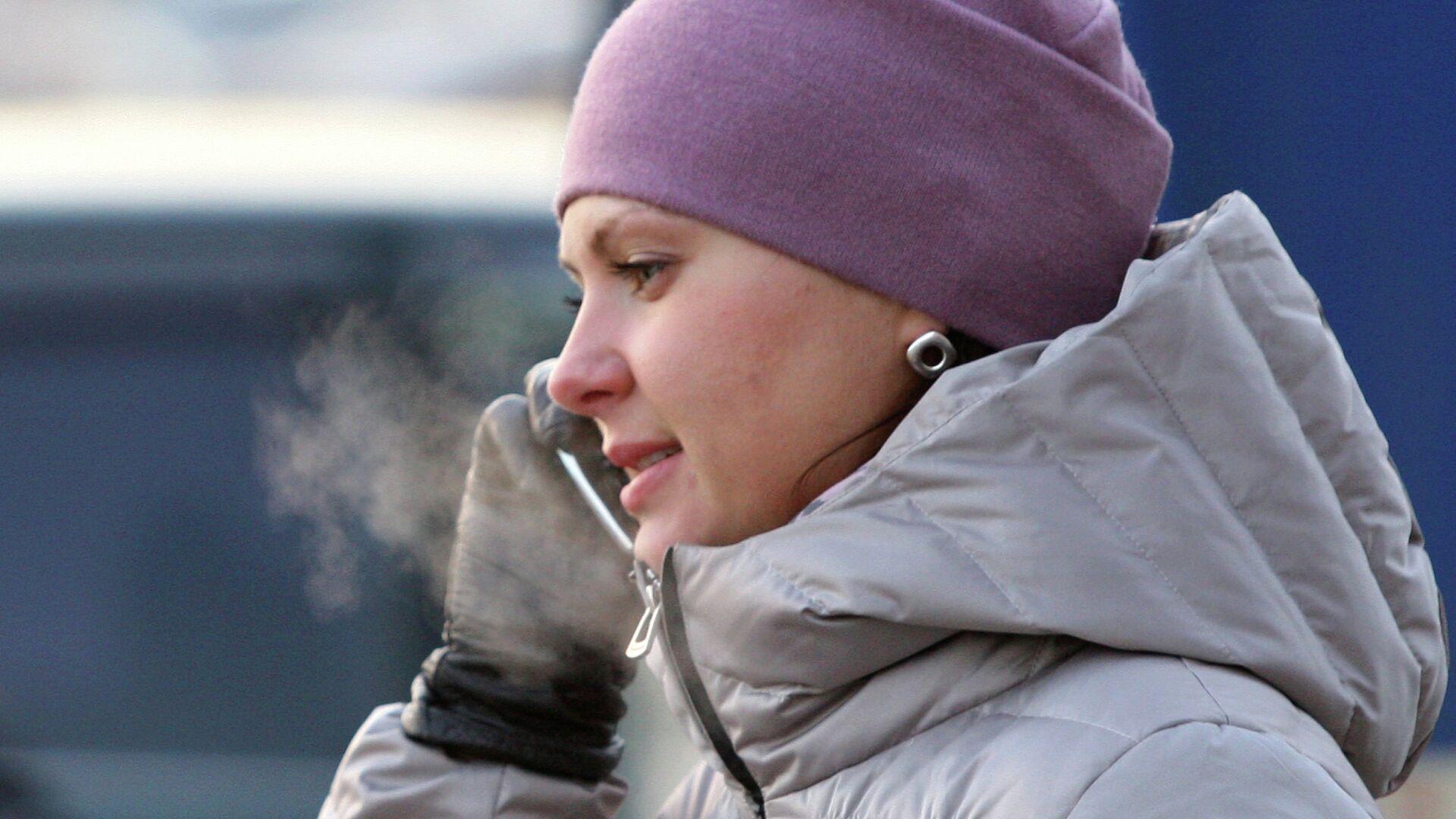 Девушка говорит по телефону в мороз на остановке автобуса в Новосибирске - РИА Новости, 1920, 05.12.2020