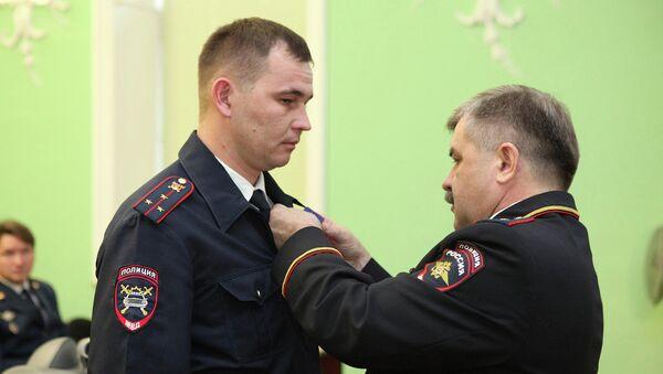 Глава МВД Башкирии Михаил Закомалдин вручает полицейскому Евгению Куклину награду За доблесть в службе