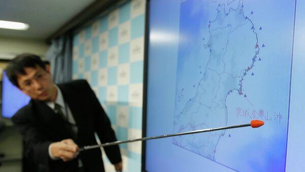 Старший координатор Японского метеорологического агентства по сейсмологической информации Макото Сайто указывает на место землетрясения