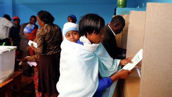 Женщина на избирательном участке в Кении