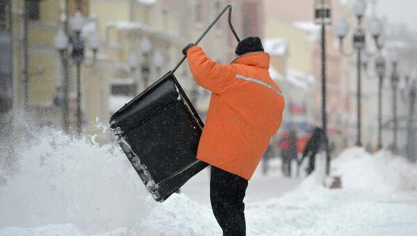 Работники коммунальных служб убирают снег после снегопада в Москве