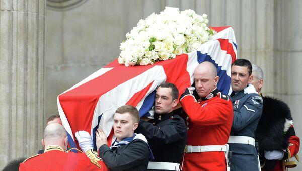 Гроб с телом экс-премьера Великобритании Маргарет Тэтчер, накрытый государственным флагом, выносят из собора Святого Павла,