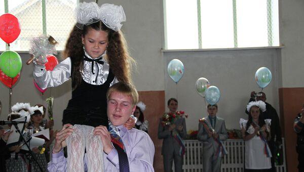 Школа села Майма (Республика Алтай). Выпускник несет на плечах первоклассницу