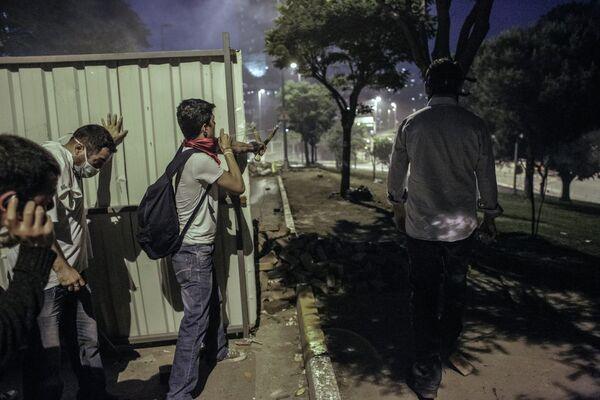 Протестующий стреляет из рогатки из-за баррикады во время столкновения с сотрудниками полиции в Стамбуле