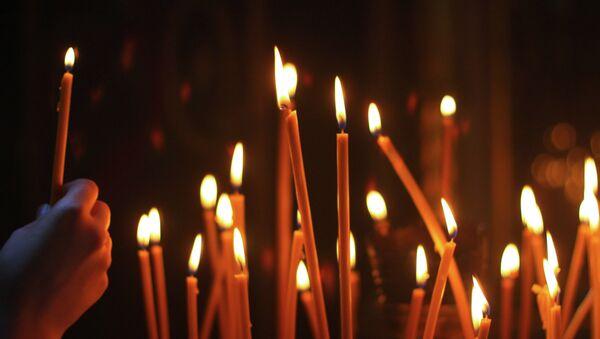 Мужчина ставит свечу в церкви