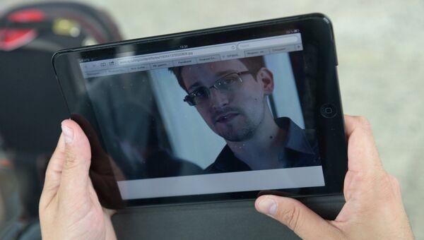 Журналист изучает фото бывшего сотрудника ЦРУ Эдварда Сноудена в аэропорту Шереметьево