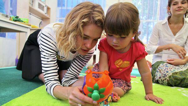 Топ-модель, учредитель фонда Обнаженные сердца Наталья Водянова общается с ребенком на открытии детской площадки в рамках ее благотворительного визита в Крымск