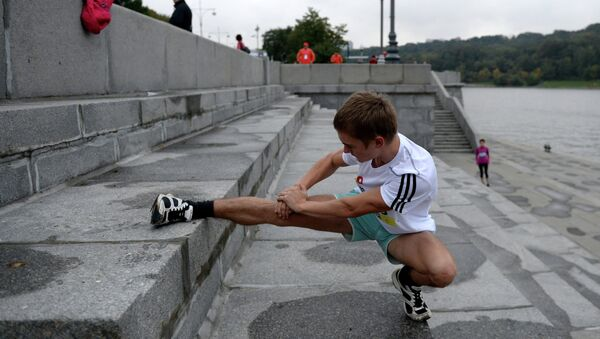 Участник Московского марафона разминаются перед забегом