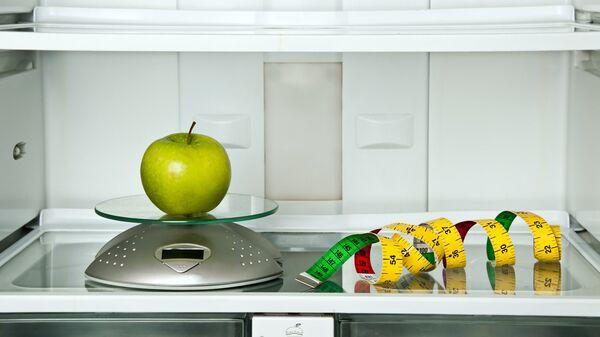 Яблоко и сантиметр в холодильнике