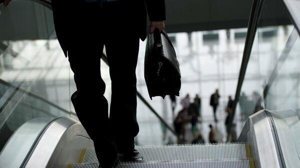 Мужчина с портфелем на эскалаторе
