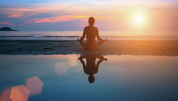 Девушка медитирует у морского побережья. Архивное фото