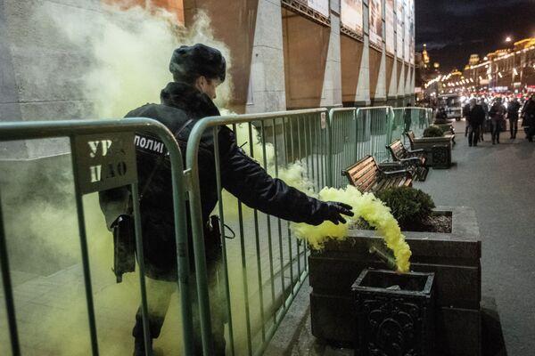 Сотрудник правоохранительных органов выбрасывает файер в урну во время акции Стратегия-31