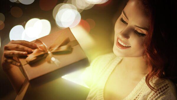 Девушка открывает подарок. Архивное фото