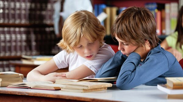 Школьники читают книги в библиотеке