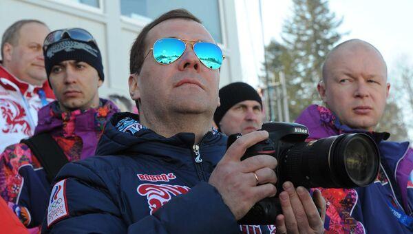 Председатель правительства России Дмитрий Медведев (на первом плане) на трибуне в лыжно-биатлонном комплексе Лаура во время мужской эстафеты по лыжным гонкам на XXII зимних Олимпийских играх в Сочи