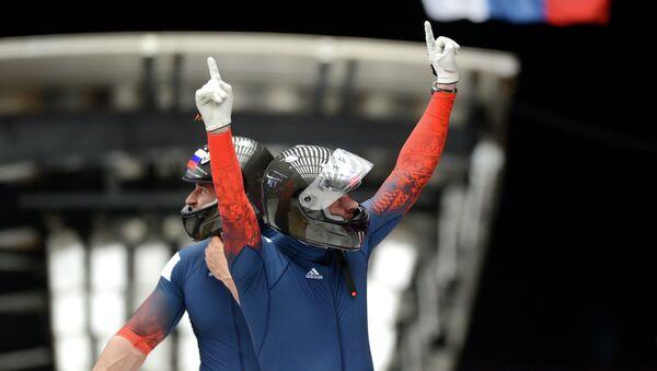 Александр Зубков и Алексей Воевода (Россия) на финише в финальном заезде двоек на соревнованиях по бобслею среди мужчин
