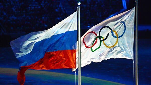 Поднятие российского флага во время церемонии закрытия XXII зимних Олимпийских игр в Сочи.