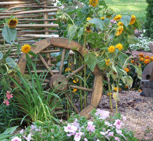 Декоративное колесо от тележки отлично украсит участок в деревенском стиле