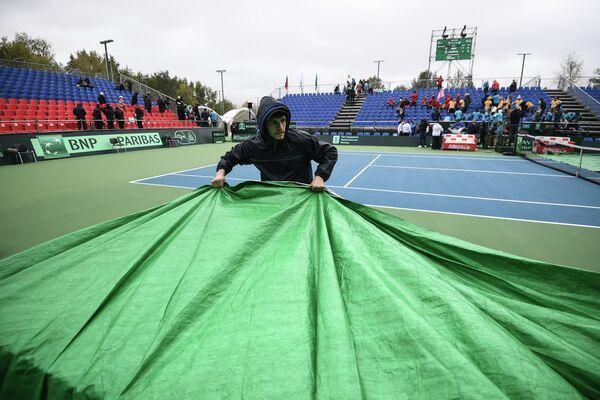 Сотрудник укрывает тентом корт Национального теннисного центра в Москве во время матча Кубка Дэвиса