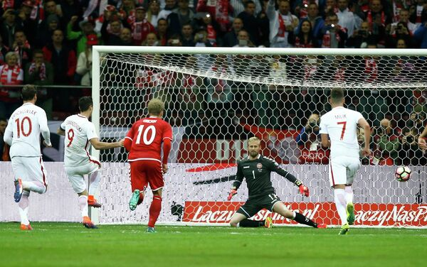 Форвард сборной Польши Роберт Левандовский (второй слева) забивает гол в ворота команды Дании
