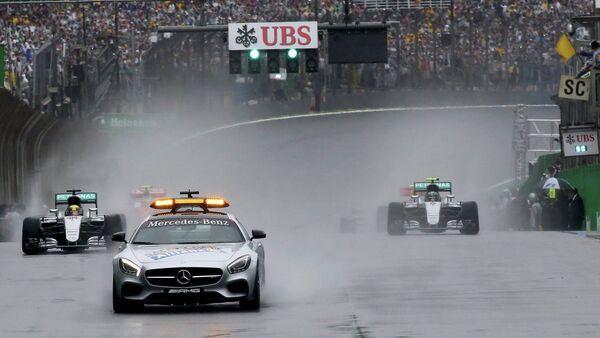 Пилот Формулы-1 следуют за машиной безопасности во время гонки Гран-при Бразилии