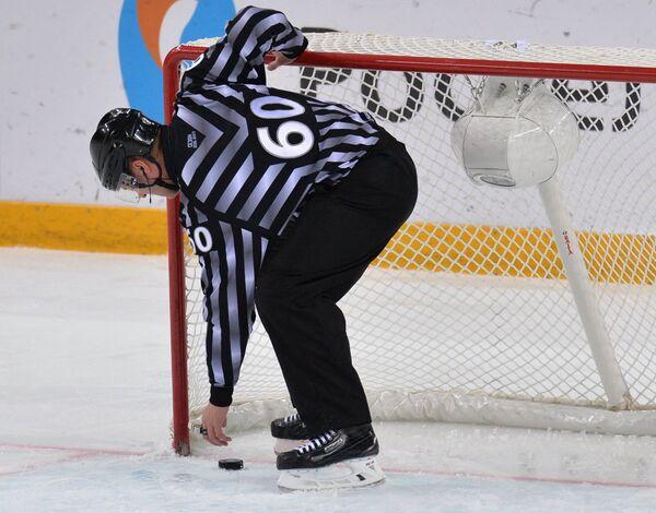 Линейный судья Алексей Михель достает шайбу из ворот в матче регулярного чемпионата КХЛ Авангард - Ак Барс
