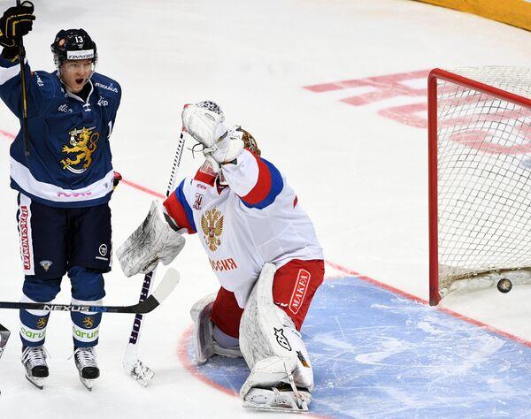 Нападающий сборной Финляндии Ессе Манкинен (слева) и вратарь сборной России Игорь Шестёркин
