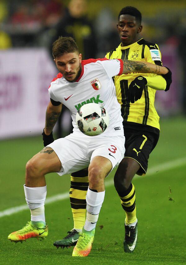 Защитник немецкого Аугсбурга Костас Стафилидис и полузащитник дортмундской Боруссии Усман Дембеле (слева направо)