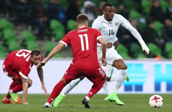 Нападающий сборной Кот-д'Ивуар Джонатан Коджиа и полузащитник сборной России Роман Зобнин (справа налево)
