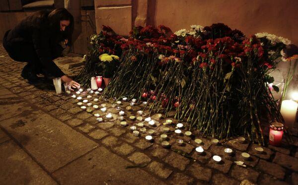 Горожане зажигают свечи у входа в вестибюль станции метро Спасская