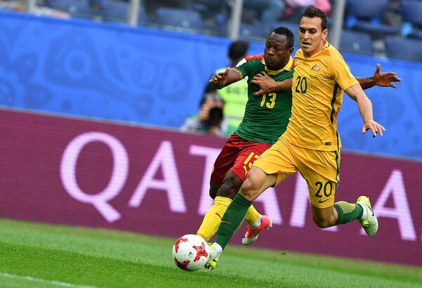 Нападающий сборной Камеруна по футболу (Камерун) и защитник сборной Австралии Трент Сейнсбери (слева направо)
