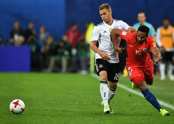 Защитники сборной Германии по футболу Йозуа Киммих и команды Чили Жан Босежур (слева направо)