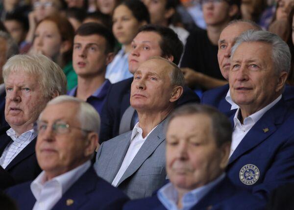 Президент РФ Владимир Путин во время посещения образовательного центра Сириус наблюдает за хоккейным матчем в рамках открытого первенства Московской области по хоккею с шайбой среди юношей 2003 года рождения. Слева на втором плане - канадский хоккеист Пэт Стэплтон, справа на втором плане - председатель Совета легенд Ночной хоккейной лиги Александр Якушев.