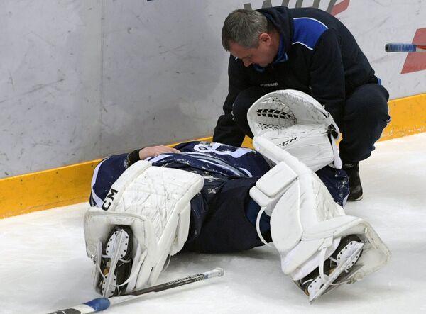Сотрудник медицинской службы оказывает помощь вратарю Динамо Ивану Бочарову, получившему травму