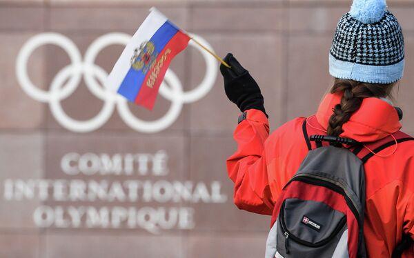 Российский флаг на фоне логотипа Международного олимпийского комитета (МОК)