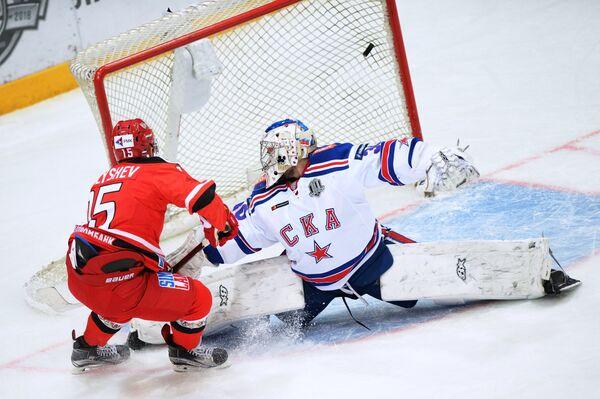 Форвард Автомобилиста Виталий Попов (слева) забрасывает шайбу в ворота голкипера СКА Игоря Шестеркина