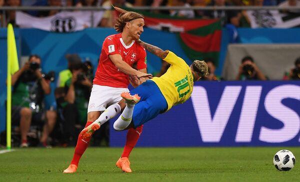 Защитник сборной Швейцарии Михаэль Ланг и бразильский нападающий Неймар (Слева направо)