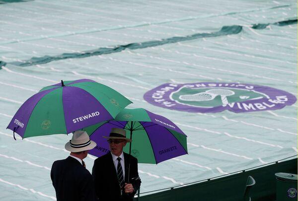Стюарды укрылись от дождя на Уимблдоне