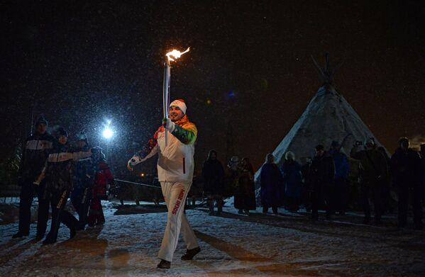 Факелоносец во время эстафеты олимпийского огня в Салехарде
