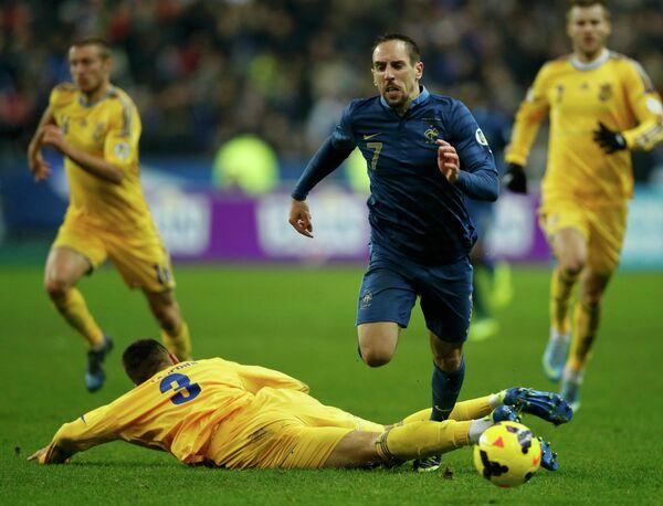 Защитник сборной Украины Евгений Хачериди сбивает полузащитника сборной Франции Франка Рибери