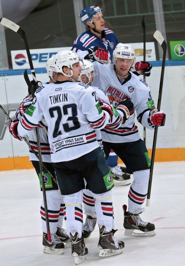 Хоккеисты Металлурга Евгений Тимкин (второй слева) и Денис Платонов (справа)