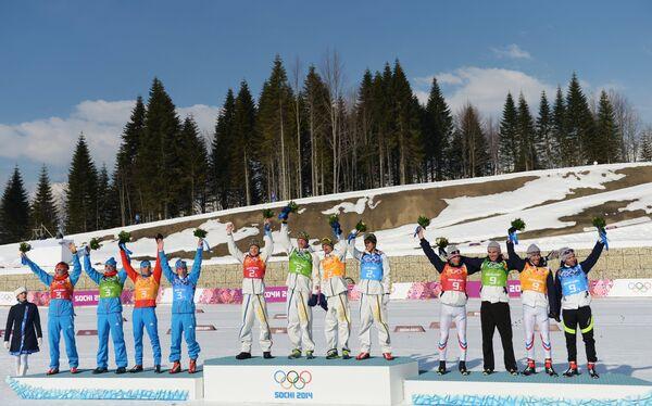 Призеры эстафеты в соревнованиях по лыжным гонкам среди мужчин на XXII зимних Олимпийских играх в Сочи во время цветочной церемонии
