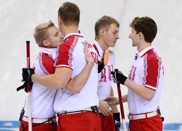 Спортсмены сборной России радуются победе в матче кругового турнира между сборными командами Германии и России в соревнованиях по керлингу