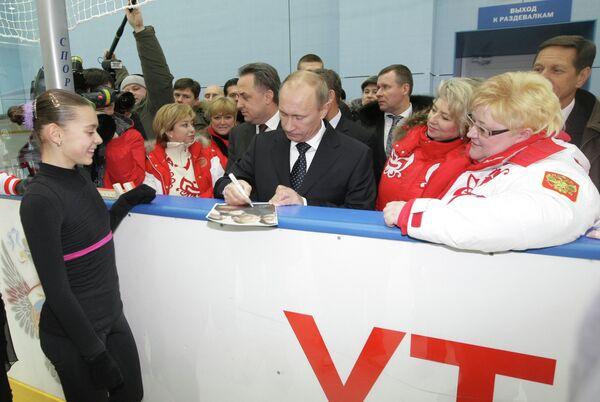 Председатель правительства РФ Владимир Путин (в центре на первом плане) дает автограф фигуристке Аделине Сотниковой (слева на первом плане)