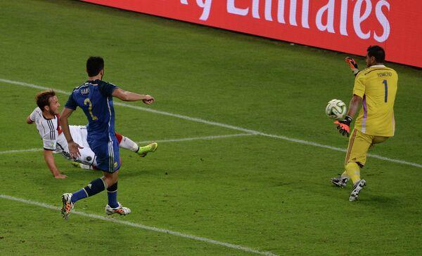 Форвард сборной Германии Марио Гетце (слева на втором плане) забивает гол в ворота Серхио Ромеро (справа)