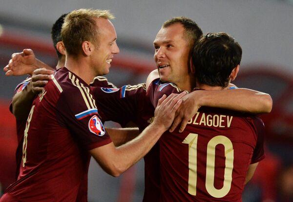 Футболисты сборной России Денис Глушаков, Сергей Игнашевич и Алан Дзагоев (слева направо) радуется забитому голу